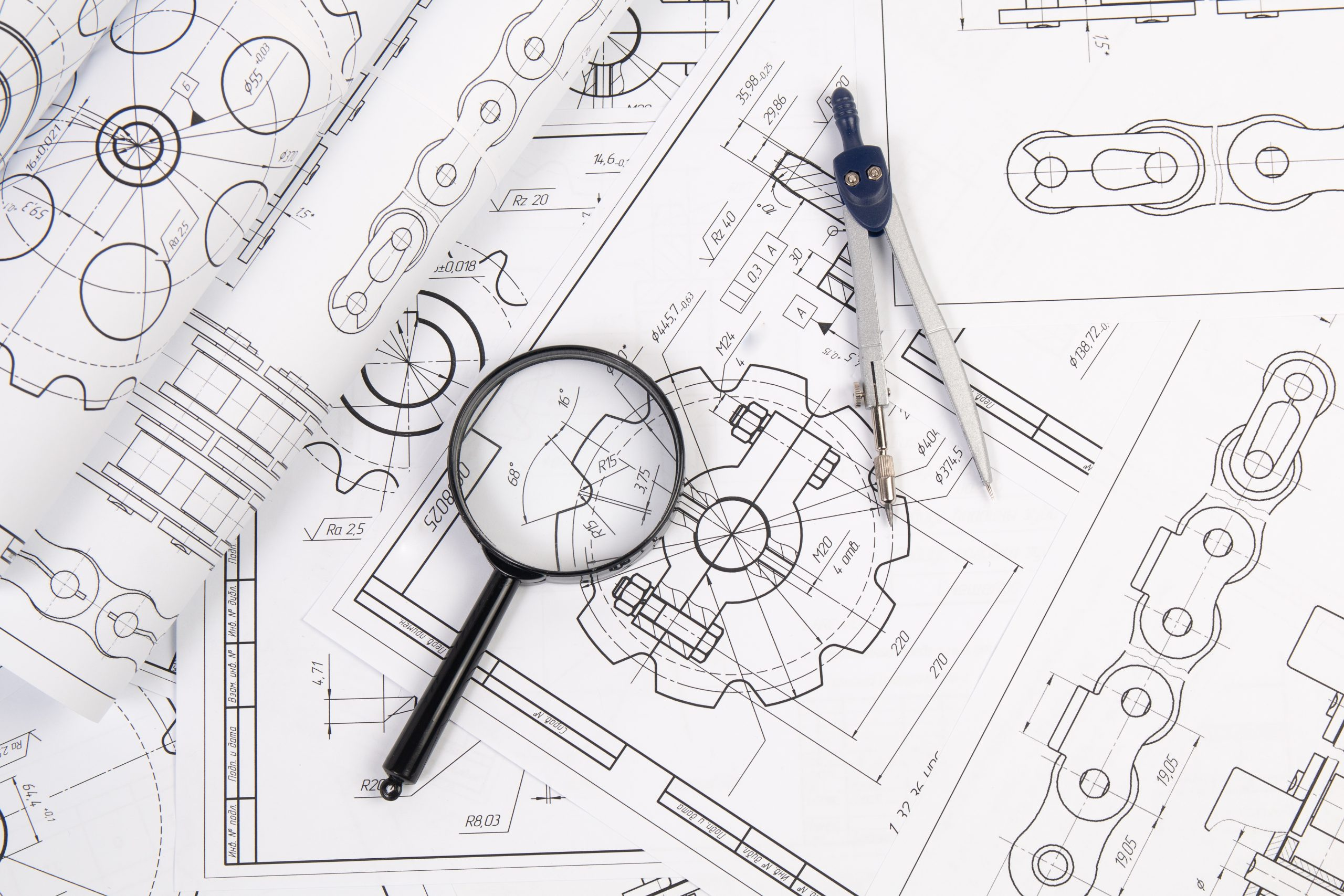 Industrial chain drawings, engineering compass and magnifying glass